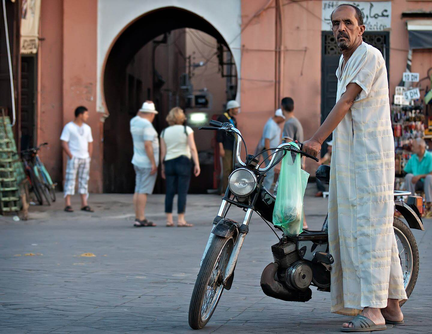 Portrait of a man dressed in djellaba with a moped