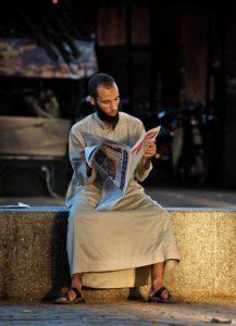 Man dressed in djellaba reading newspaper; Marrakech, Morocco - Photo by Zdenek Sindelar ~ CuriousZed