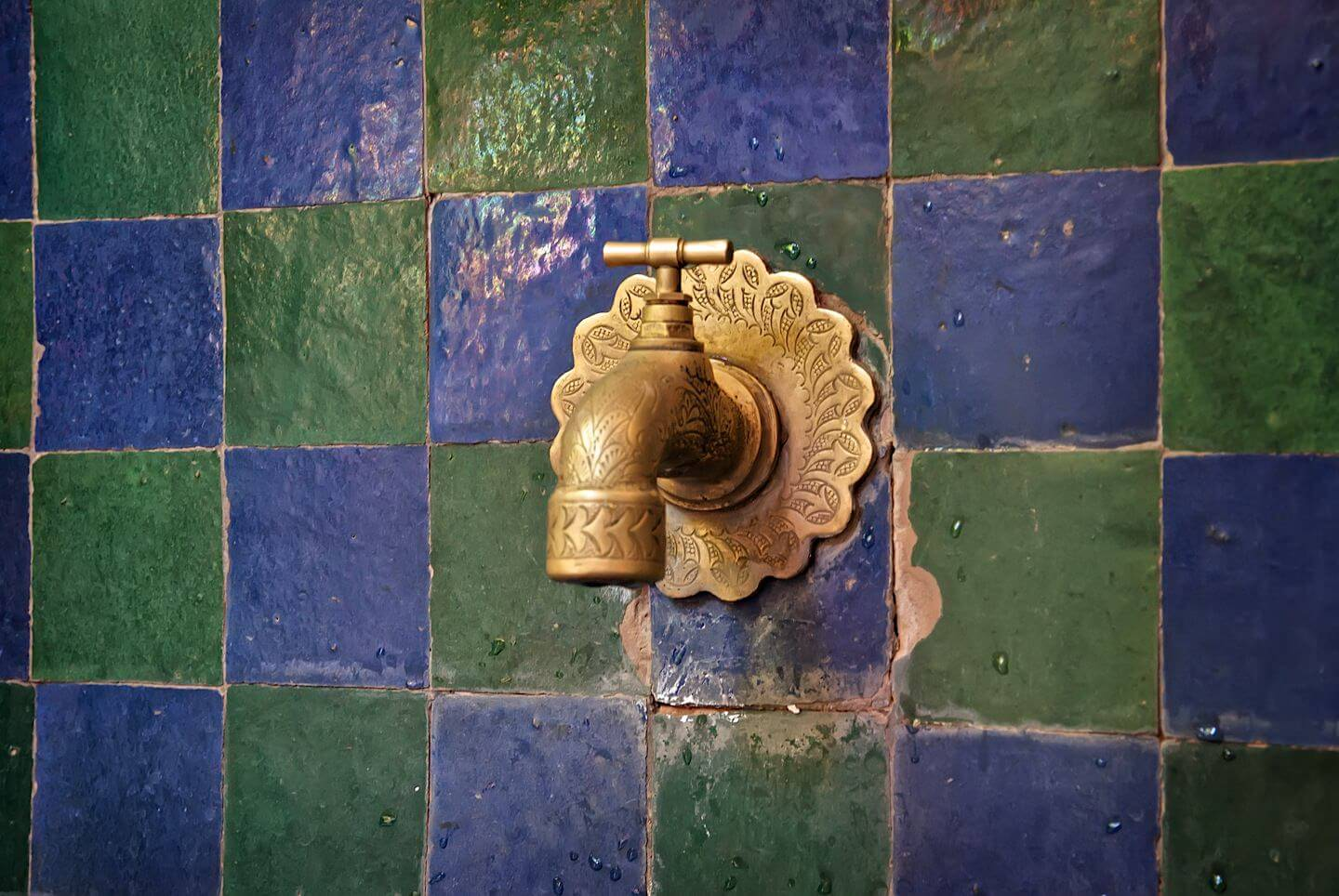 Detail of a water tap with blue/green tiles in Jardin Majorelle - Marrakech