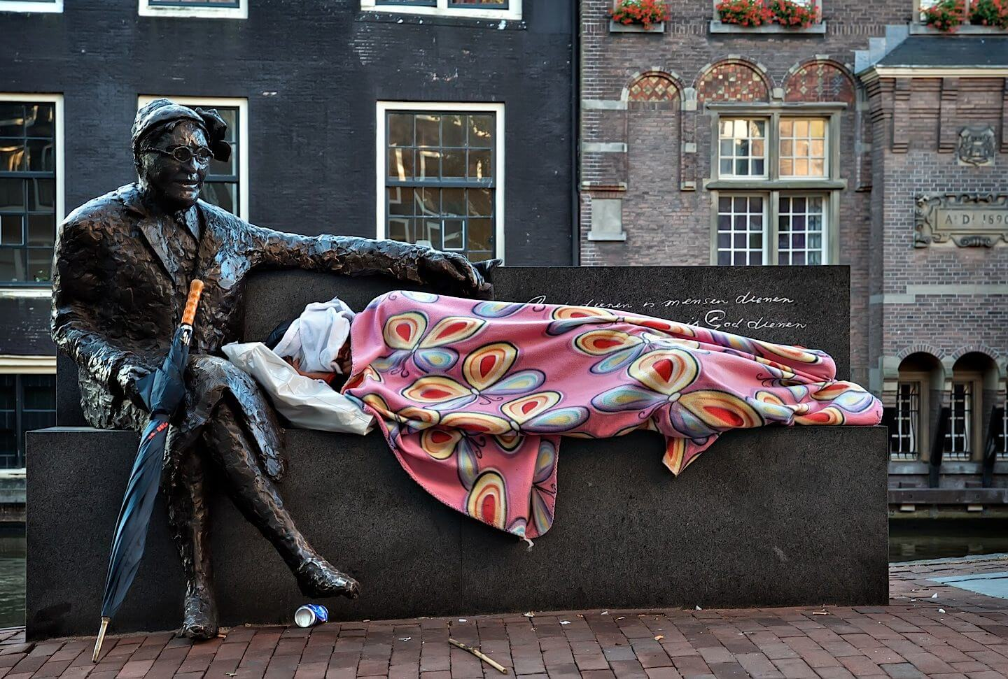 Homeless man sleeping on a bench in the Red Light District in Amsterdam next to a statue of Major Alida Bosshardt