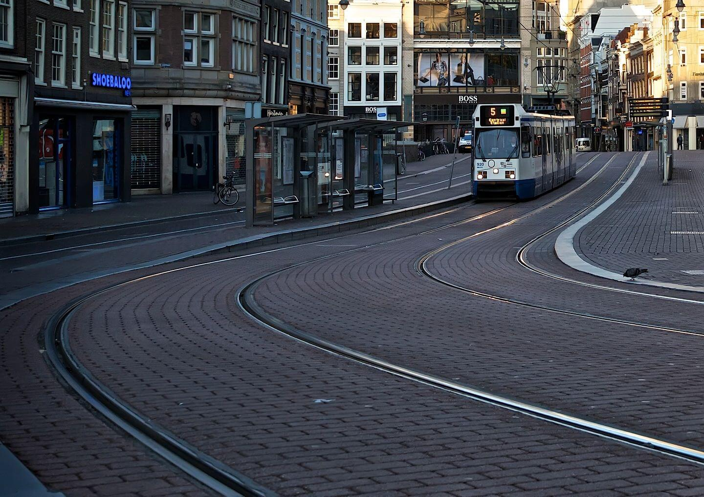 Tram on an empty Amsterdam street early in the morning
